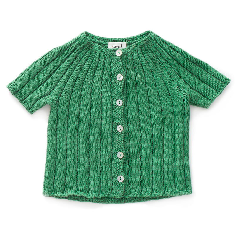 Ribbed knitted cardigan with 6 white buttons on the front. Ideal to wear with knitted shorts from Oeuf.