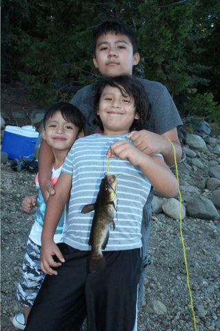 Gaiel Mendez and his two brothers show off a brown bullhead catfish that is typical of those found in Lake Valley