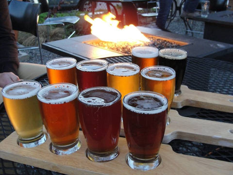 taster flight of beers next to a fire pit - Sudsy Style - beer fashion for your beer passion