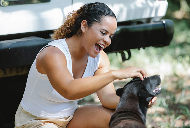 Smiling Young Woman Playing With Dog Outside Next to Car