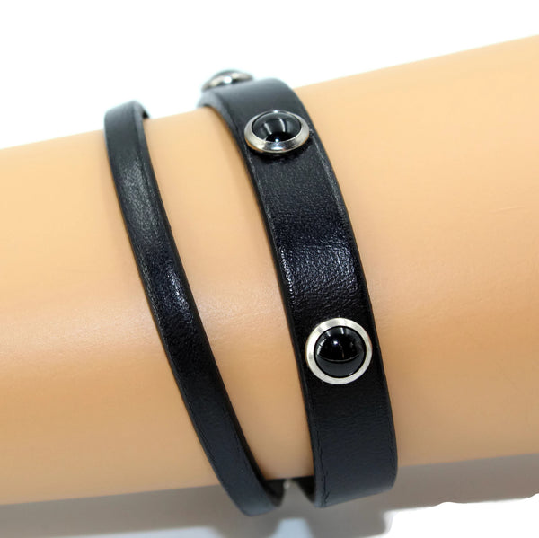 write modeling 10mm and 5mm black leather bracelets. 10 mm adorned with jet cabochon studs, handmade by arthlin jewelry