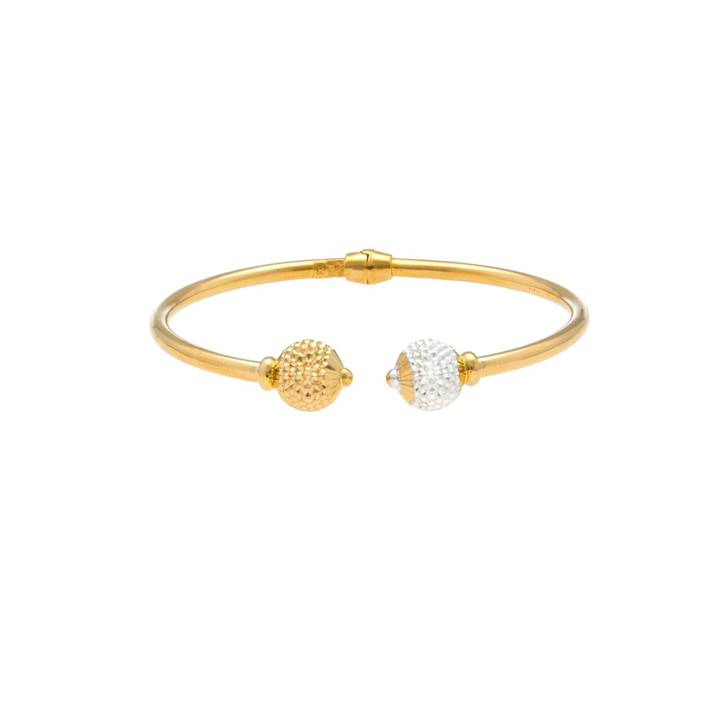 An image of a 22K gold bangle with contrasting white and yellow gold beads at the ends from Virani Jewelers. | Complete your look with this gorgeous 22K gold bracelet from Virani Jewelers!  Featuring yellow a...