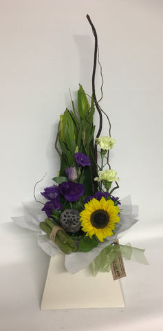 Arrangement featuring sunflowers in purples and green