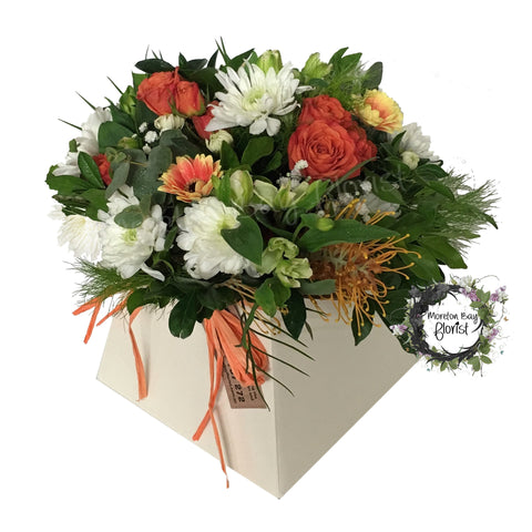 Lush flower arrangement in creams, whites and orange