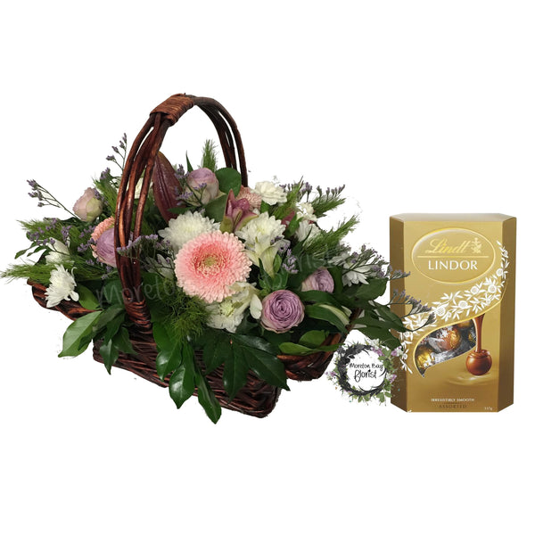 Basket arrangement of pink and white seasonal flowers with chocolates