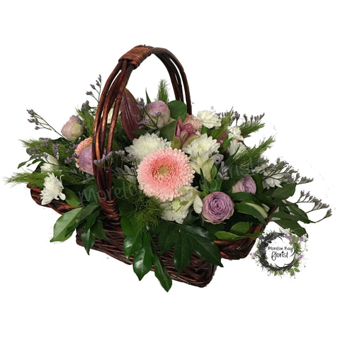 Basket arrangement of pink and white seasonal flowers