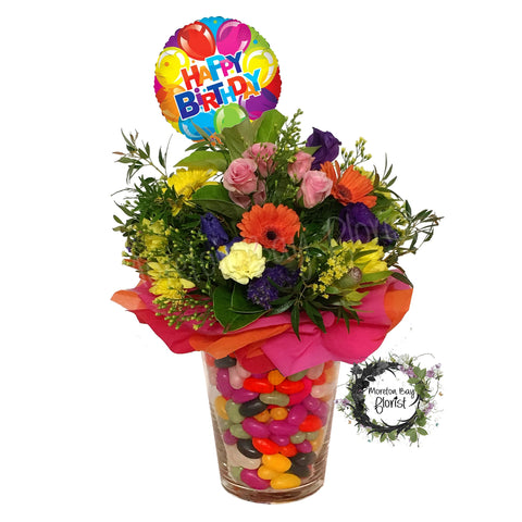 Colourful flower arrangement in jelly bean vase with birthday balloon