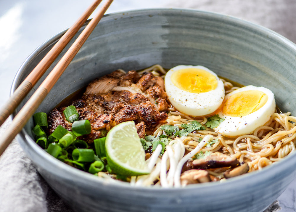 Bowl of ramen with lime and egg on top
