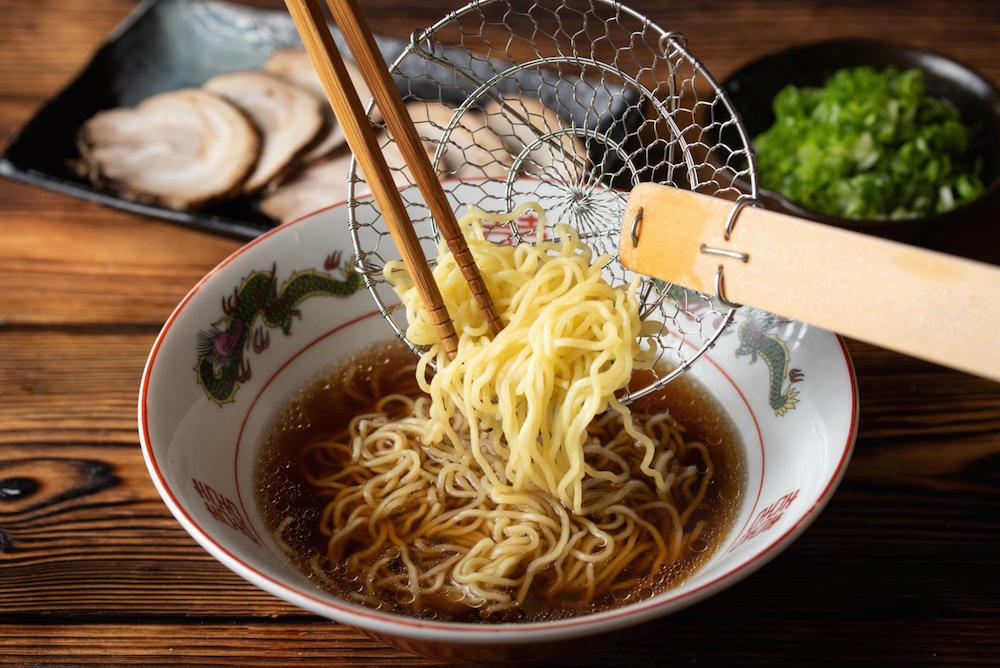 Ramen noodles being scooped into a bowl