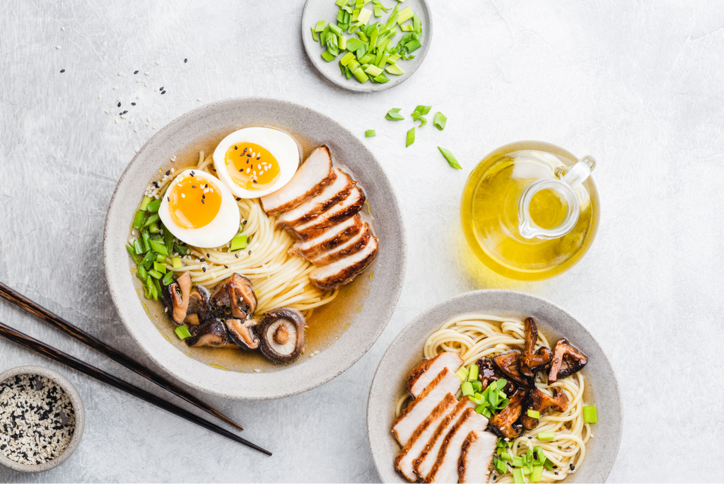 Two bowls of ramen with bottle of oil and chopsticks