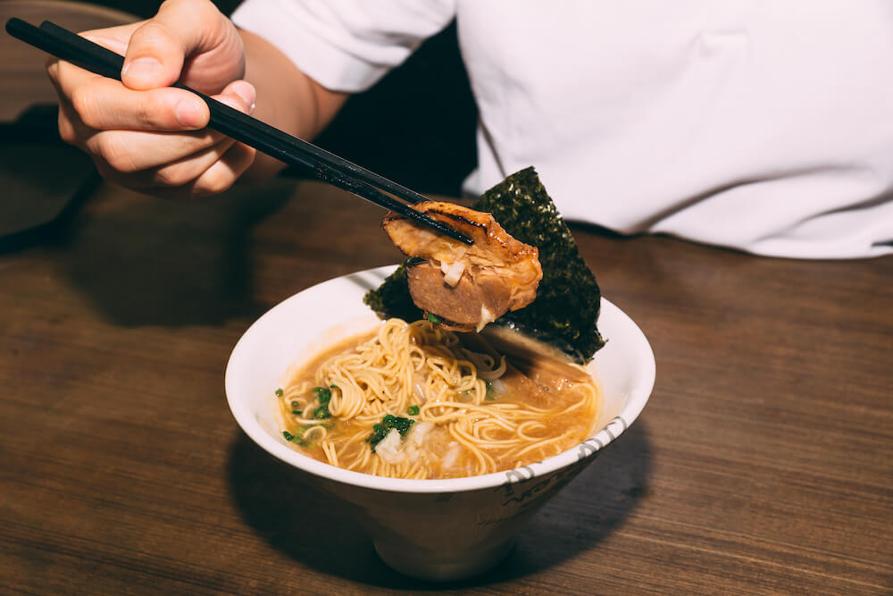 How to eat ramen: Person picks up toppings with chopsticks