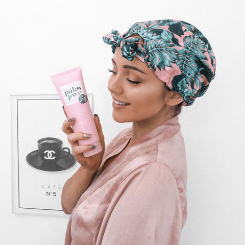 Woman holding Coconut Lane Palm Pwr product in pink dressing gown