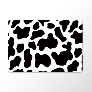 black and white cow print on a macbook case with white background