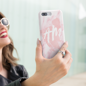 Female holding pink phone case with initials
