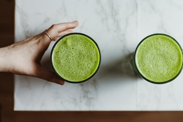 Two glasses of green supplement drink on counter