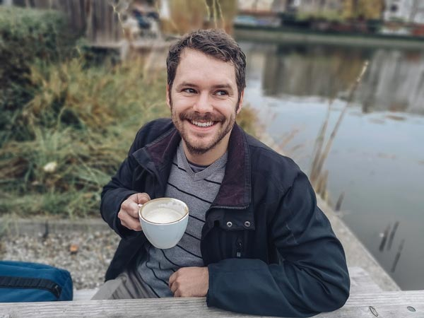 man smiling with coffee cup outside