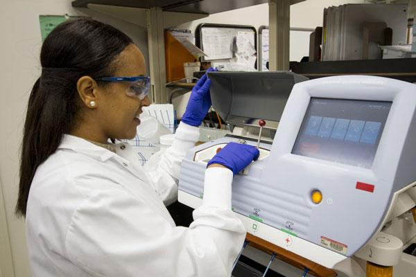 laboratory technician works on a lab processing machine