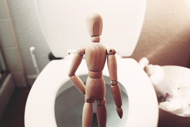 wood figurine in front of a toilet