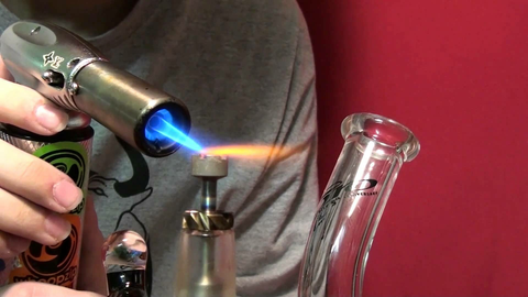 Dabbing torch and domeless titanium nail on a water pipe