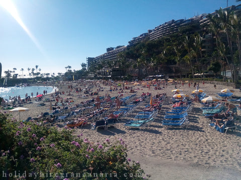 White Beach Anfi del Mar in Gran Canaria with sunbeds, umbrellas, people and big hotel