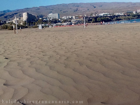 beach Playa del Ingles with a lot of sand and view of the mountain and hotels in Canary Islands