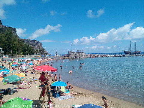 Beach in Mogan harbor in Gran Canaria, almost withe sand and azure water with view of rocky coast