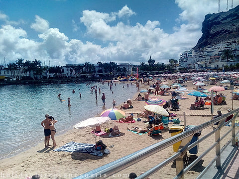 Beach in Mogan Gran Canaria Island with sandy coast and panorama harbor and hill with white apartments