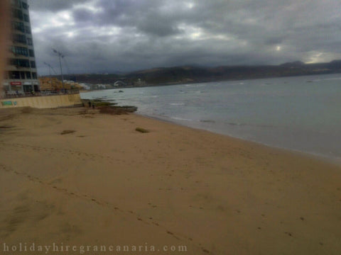Las Palmas in dark day with dark clouds and black ocean and sandy beach Canteras