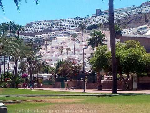 Town Puerto Rico with view of cascade buildings and green jardin in front in Gran Canaria