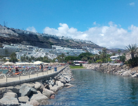 Stone canal in Puerto Rico in Gran Canaria with panorama the town in Canary