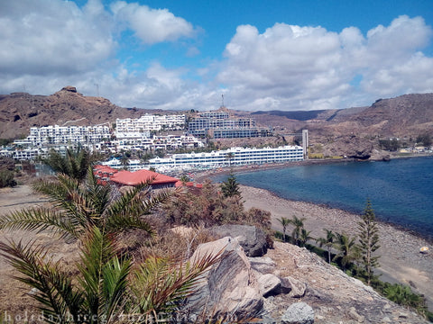 Panorama Tauro with blue bay and buildings of hotels and two beaches with yellow and gray sand Gran Canaria Canary