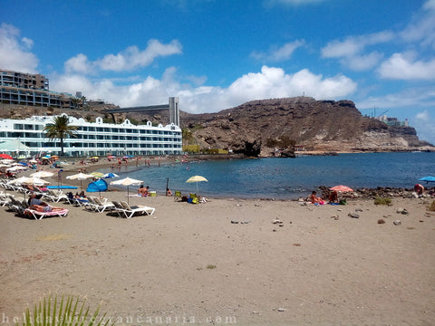 Gray beach in Tauro with view on blue bay with stone hill and white hotel