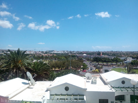 View on Maspalomas and ocean from apartment white houses and a lot of green plants and palms