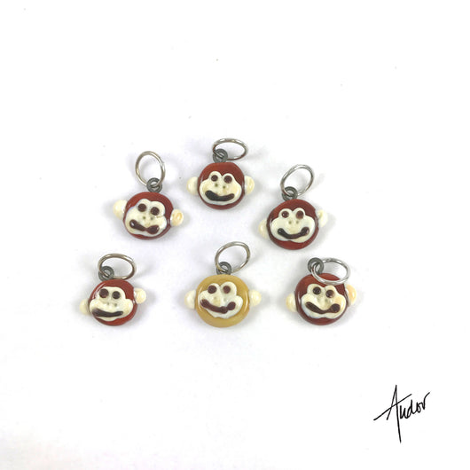 Set of 6 cute monkey stitch markers.  One is a tan for a row markers and the others are brown, all with silly grins!