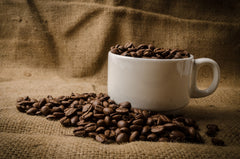 Cup of coffee on a burlap sack surrounded by roasted coffee beans.