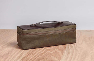 Olive green waxed canvas snack pack with brown leather top and handle