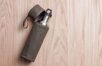 Stainless steel flask water bottle peeking out of Otter Pass olive green lined bottle holder