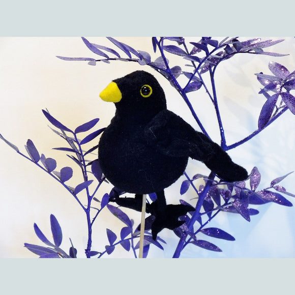 Blackbird finger puppet, soft black fabric with yellow beak.