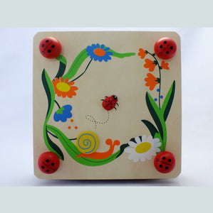 Wooden flower press decorated with flowers and ladybirds.