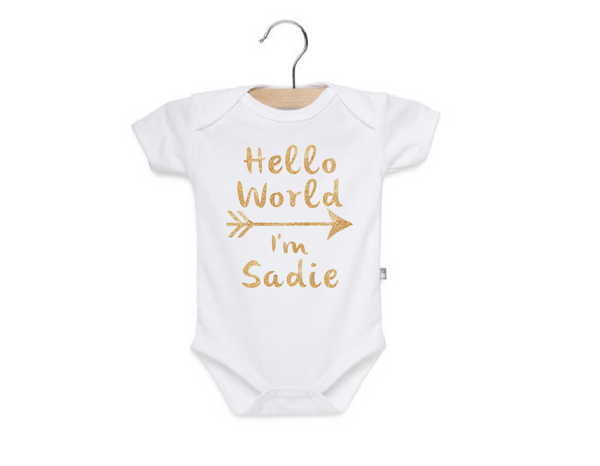 white onesie with gold glitter writing hello world i'm sadie. Customized newborn coming home outfit