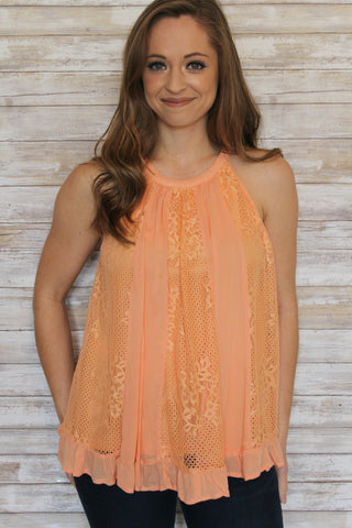 Peach halter top with ruffle and lace in the front.