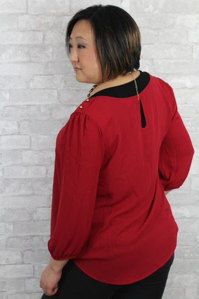 Burnt red 3/4 sleeve plus size top, with keyhole back and gold button detail on the shoulders.