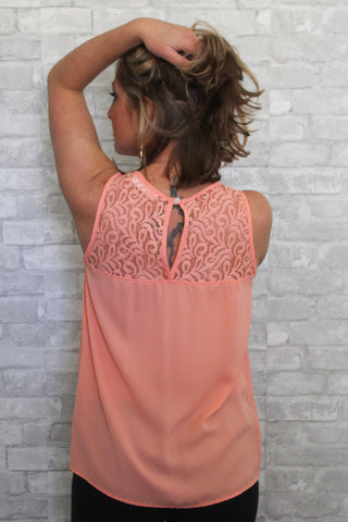 Peach tank top with lace on the top of the shirt.