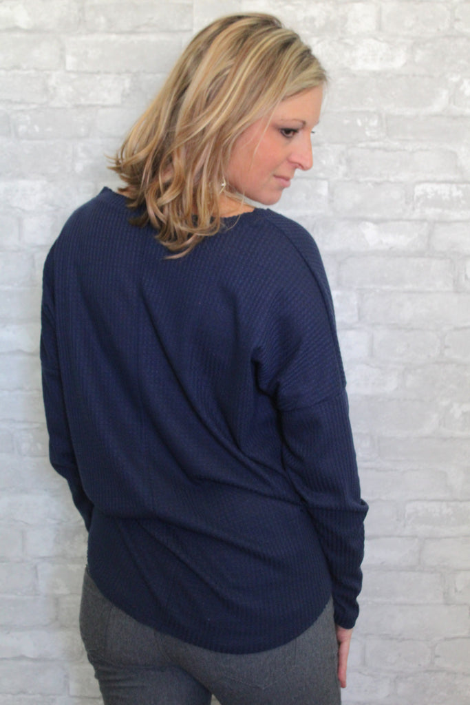 Navy waffle knit long sleeve v-neck top with self-tie detail in front.  Lightweight and comfortable.