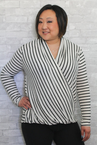 A long sleeved black and white sweater with a criss cross front.