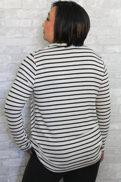 The back side of a long sleeved black and white sweater.
