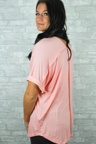 Blush pink v-neck top with folds on the end of the short sleeve.