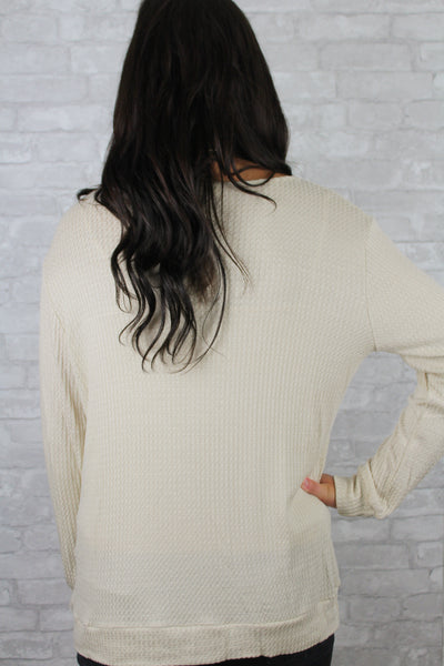 Back side of a soft tan sweater.