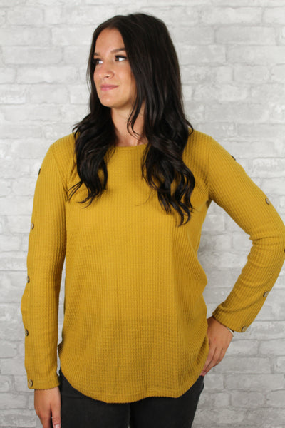 Front side of mustard waffle knit sweater with button sleeves.