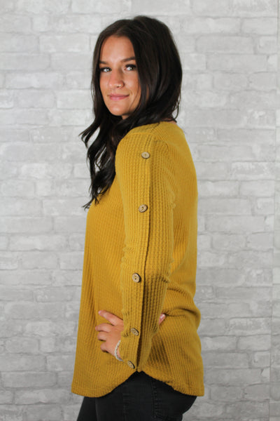 Side view of mustard waffle knit curvy sweater with button sleeves.